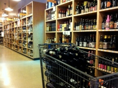 A shopping cart of beer and lots of the hard stuff nearby!